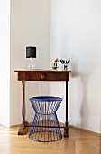 Blue wire stool at antique writing desk in corner of minimalist living room