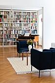 Loungebereich vor antikem Klavierflügel und raumhoher Bücherwand in Altbauwohnung