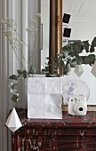 Branches in paper bag on mantelpiece