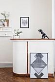 Artwork leaning against half-heigh wall with dinosaur figurine on bar above