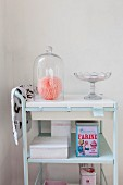 Glass cover and retro tins on pale blue serving trolley
