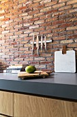Backsteinwand mit Messerleiste über grauer Küchenarbeitsplatte