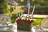 White candles in candleholder hand-made from twigs red flowers and leaves on festively set table outdoors