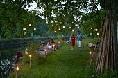 Party atmosphere in garden; guests amongst torches and lanterns hung from trees