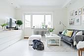 Helles Wohnzimmer mit Blick auf Fenster und Balkontür, weisses Sideboard mit Fernseher, Polsterhocker, Couchtisch und graues Sofa