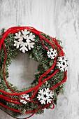 Kranz mit Schneeflocken aus Holz und roter Kordel
