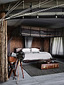 African style bedroom with straw walls and modern mosquito canopy