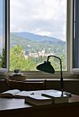 Blick über Schreibtisch mit nostalgischer Tischleuchte und Büchern auf Hügellandschaft