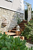 Garden sink on stone outside wall of renovated country house and white lanterns on treads of cedar-wood steps