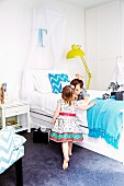 Children with wrapped presents in bedroom with white beds and elegant flair