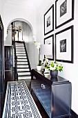 Schwarz-weißer Treppenaufgang in elegant renovierter Altbaudiele mit Rundbogen