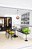 White lacquered built-in bench under photo gallery in elegant black and white living area with yellow color accent and passage