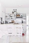 Open kitchen with white kitchenette, wall tiles and kitchen counter
