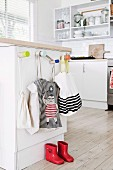 Children's wardrobe at kitchen counter with fabric bags and red children's rubber boots on plank floor