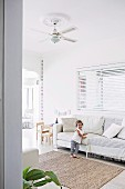 Little girl on bright upholstered sofa in living room with children's play area and colorful garland