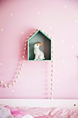 Rabbit figure on house-shaped shelf with pearl necklace on pink wall