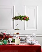 A table decorated for Christmas with a red tablecloth and white crockery, a Christmas wreath hanging above