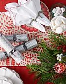 Gebäck in Schalen neben Teller mit Stoffservietten und Silberring auf weihnachtlich geschmücktem Tisch