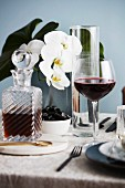 Red wine glass and crystal carafe, white orchid on table in background