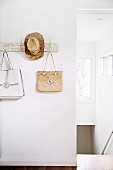 Vintage wall hook bar with hanging pockets and straw hat