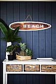 White wall table with storage baskets in front of dark blue wooden wall and maritime sign