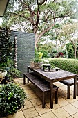 Table and bench set on a green terrace in front of box hedge and screen wall