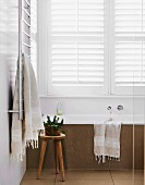 Steinverkleidete Badewanne in reduziertem Bad mit weißen Jalousieläden und rustikalem Holzhocker
