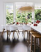 White kitchen counter with wicker bar stools in front of a set dining table and garden view