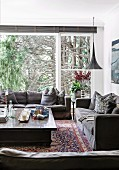 Cozy living room corner with gray sofa set in front of window and view of trees