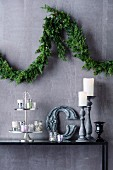 Christmas branch garland on wall above decorative arrangement with tea light glasses and candle holders