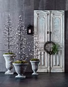 Three stylized decorative trees with light decoration in amphorae, vintage cupboard door with wicker