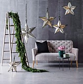 Illuminated decorative stars hung from elegant chains on metal chains and twig garland draped over stepladder