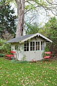 Red metal chairs outside grey wooden summer house in autumn garden