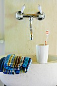 Toiletries on stone sink below vintage-style, wall-mounted taps