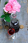 Glass and carafe of wine next to vase of pink roses on vintage wooden surface