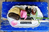 Sponge, toiletries, hair brushed and rose on white tray on blue wooden board