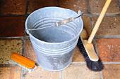 Metal bucket, broom and scrubbing brush on terracotta floor