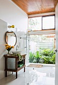 Antique vanity furniture in front of a tiled wall with a round mirror next to a glass shower partition and a view of the green patio