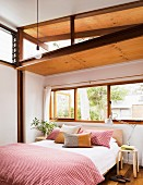 Bright bedroom with Asian and European flair; Double bed with red and white checked bed linen and pillows in front of a window hinge