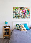Boy's room with vintage bedside tables, illuminated globe and colorful comic poster over headboard