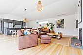 Open living area with leather sofa and fireplace, in the background dining area and fitted kitchen