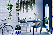 A laid table in a cool, blue ambience with green plants and a round arch