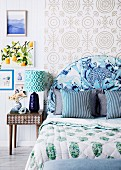 Bedroom in a mix of patterns; Bed with blue upholstered headboard in front of pattern wallpaper and retro bedside table with table lamp