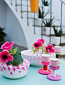 Colourful table decorations: bowls of anemones criss-crossed with washi tape and stands hand-made from jar lids and thread reels