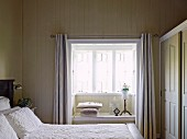 View over double bed with white bedspread in wooden bedroom to window niche