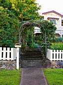 Rose arch over garden stairs and white picket fence in front of a Queenslander-style country house