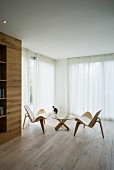 Minimalistisch möblierter Wohnraum mit Designermöbeln und Eichenboden