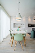 Dining table and mint-green shell chairs in white designer kitchen