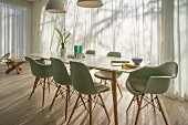 Elegant table and green classic chairs in front of windows with airy curtains