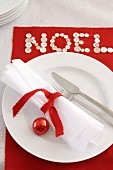 Weihnachtsgedeck mit weisser Serviette und roter Christbaumkugel